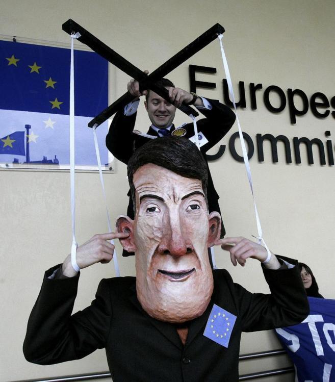 Un manifestante manipula una marioneta del comisario europeo Peter...