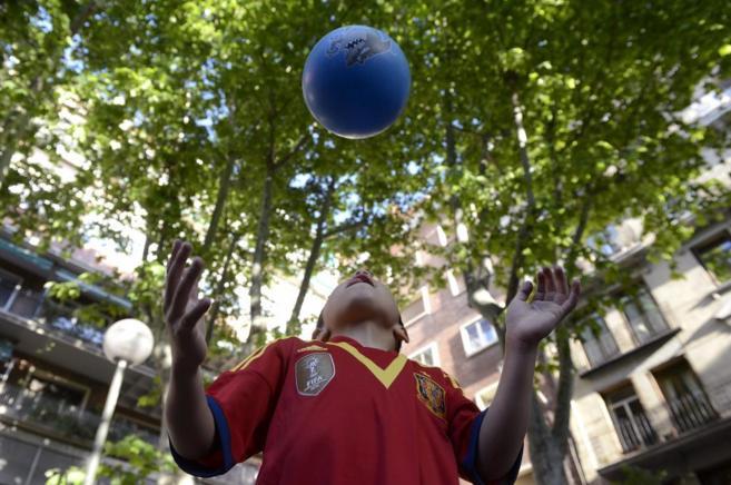 Un niño mira al cielo mientras juega con una pelota