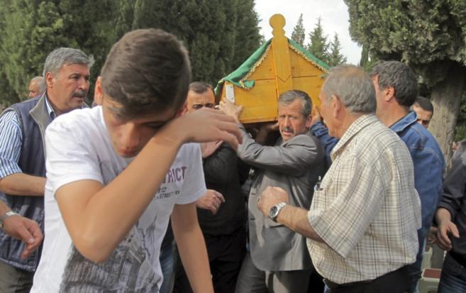 Familiares de las víctimas llevan a hombros un féretro de uno de los...