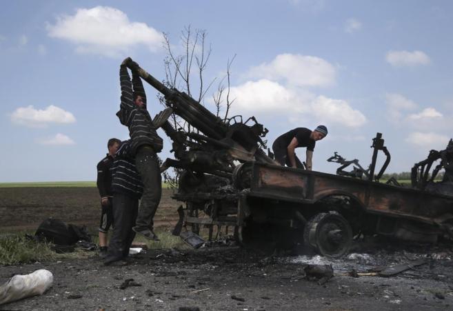 Militantes prorrusos registran un vehículo militar quemado en la...