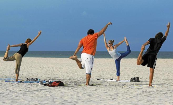 Gente practicando yoga en la playa.