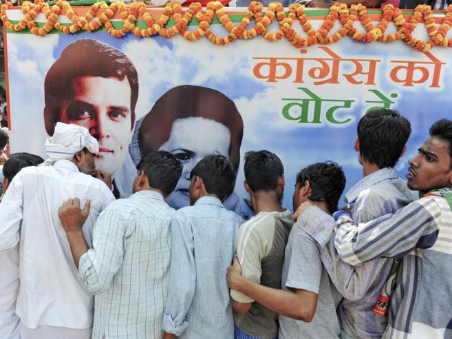 Varios hombres delante de uno de los póster de campaña de Rahul y...