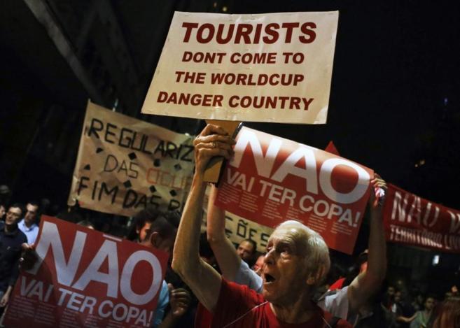 Manifestantes muestran pancartas con mensajes de protesta por el...