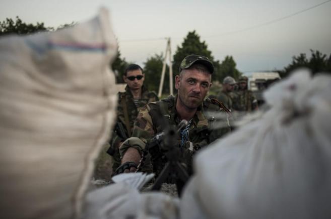 Militantes prorrusos armados montan guardia en un punto de control...