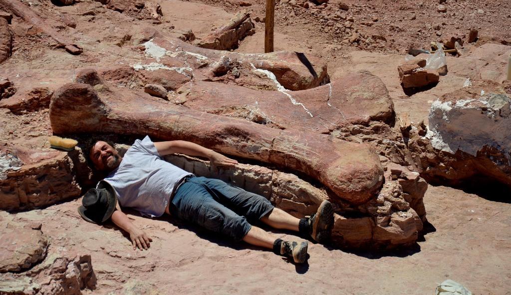 Uno de los investigadores junto a un fémur de un dinosaurio.