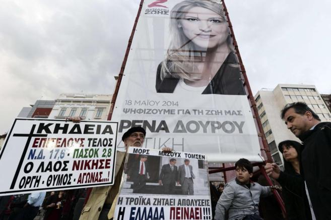 Un hombre con carteles contra la Troika durante un mitin electoral.