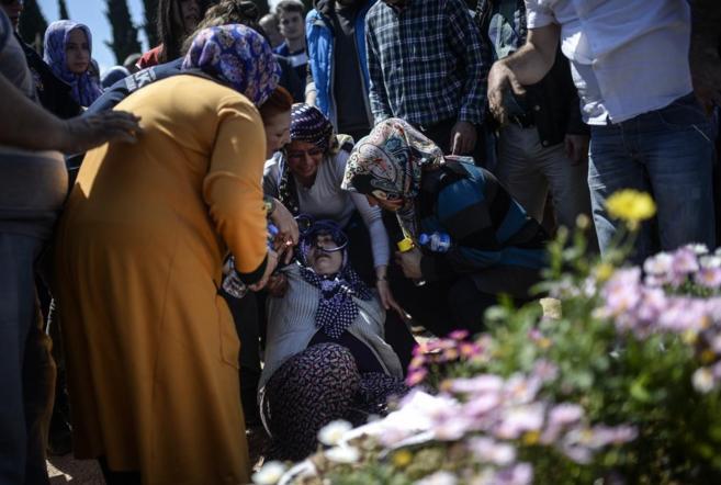 La madre de una víctima pierde el conocimiento durante el entierro de...
