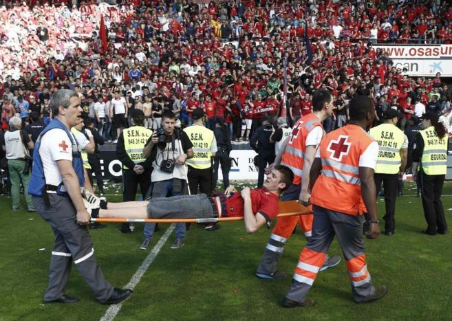 Efectivos de Cruz Roja trasladan en camilla a uno de los heridos en el...