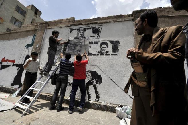 Un hombre observa a activistas pintando un mural en Saná contra la...