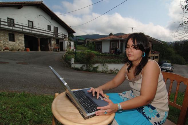 Una joven con un ordenador portátil.