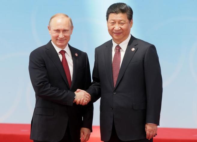 El presidente ruso, Vladimir Putin (izda.), y su homólogo chino, Xi...