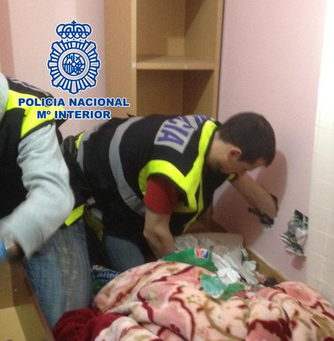 Dos agentes buscan paquetes de droga entre los huecos de una pared.