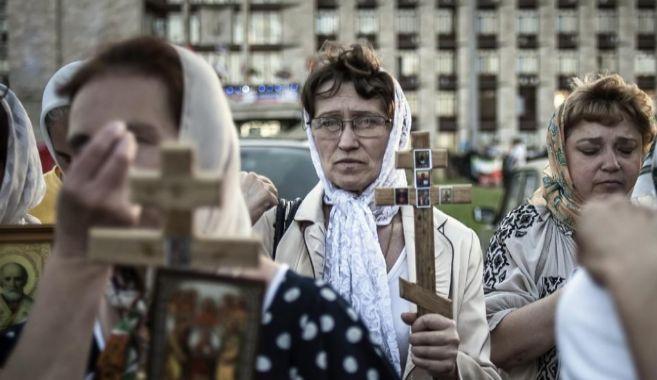 Mujeres ucranianos cruficijos oran en una ceremonia en Donetsk...