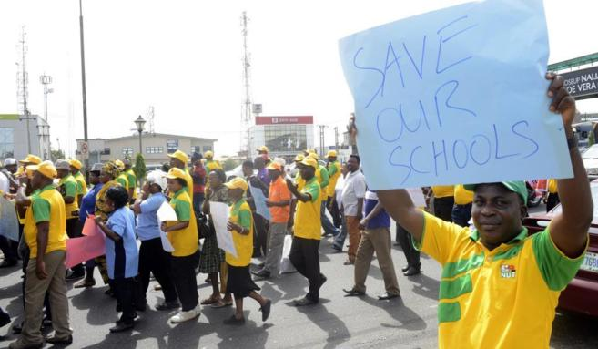 Un profesor nigeriano sostiene una pancarta en la que se puede leer...