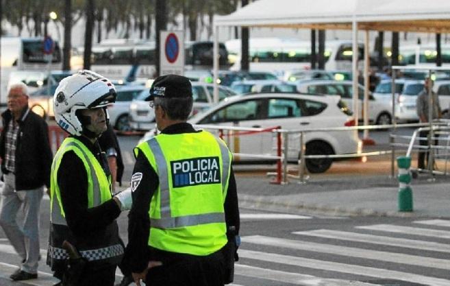 Dos policías hablan frente a la parada de taxis del aeropuerto de Son...