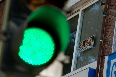 Un semáforo en verde delante de un piso con un cartel de 'Se...
