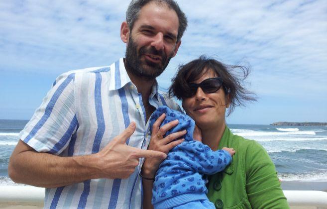 Una pareja posa en la playa con un bebé en brazos