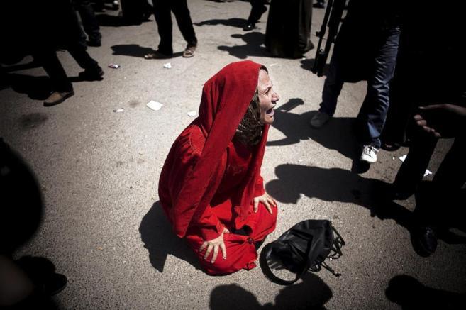 Una mujer, que perdió a un hijo durante la revolución, grita de...