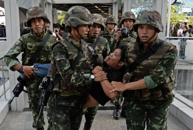 Un manifestante pro-democracia es detenido por los militares en...