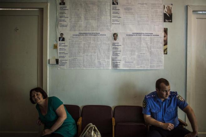 Una mujer ucraniana y un policía, sentados en un colegio electoral en...