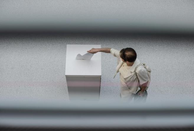 Una mujer deposita su voto en Polonia.