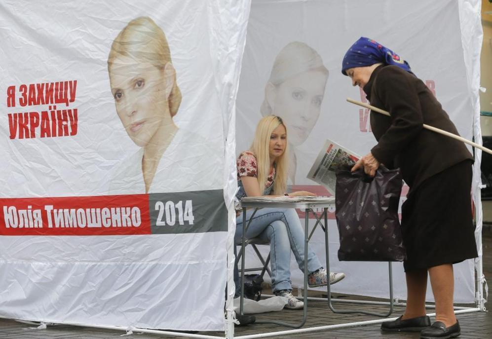 Una mujer de avanzada edad recoge propaganda electoral en un puesto...