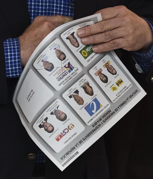 El ex presidente Uribe, con una papeleta en la mano.