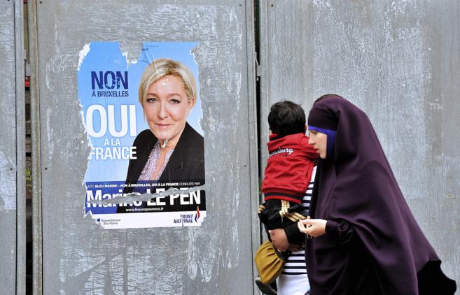 Dos mujeres musulmanas caminan por delante de un cartel electoral de...