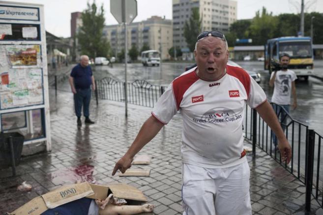 Un hombre señala el cadáver de una mujer en Donetsk.