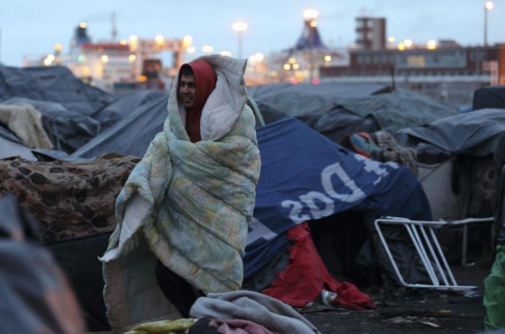 Un inmigrante afgano protegiéndose del frío durante su desalojo del...