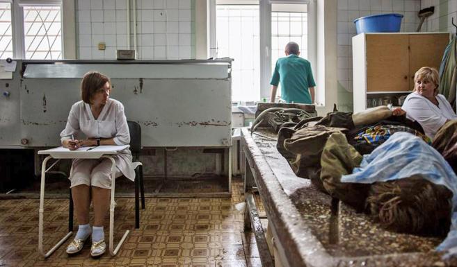 Médicos y enfermeras ucranianos se preparan para limpiar el cadáver...