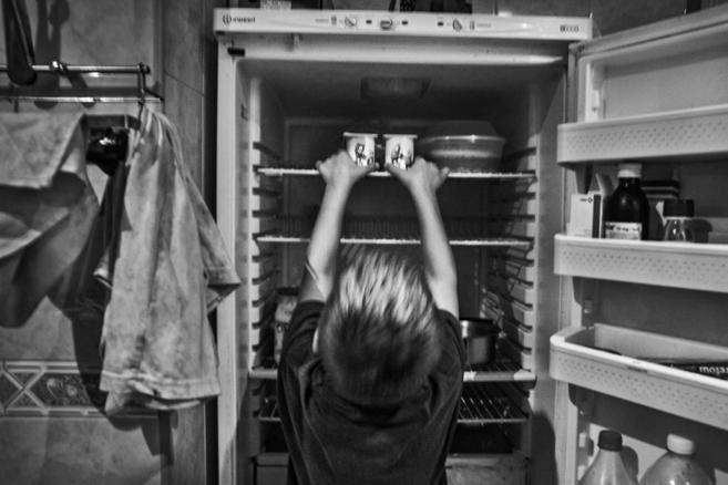 Un niño de Valencia abre el frigorífico de su casa.