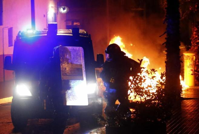 Un mosso junto a un container incendiado en los disturbios de Can...