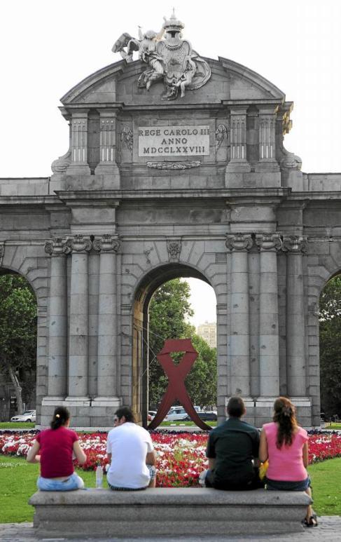 La Puerta de Alcalá, con el lazo rojo que simboliza la lucha contra...