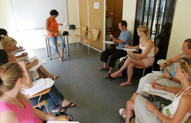 Varios alumnos extranjeros estudian español en una academia.