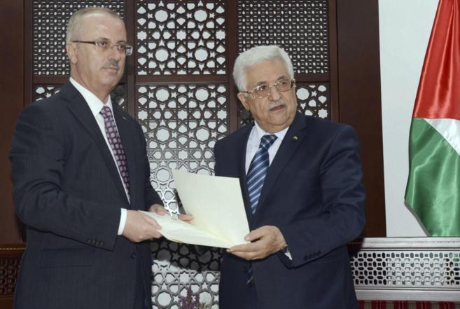 Jefe del GObierno de Al Fatah, Rami Hamdallah (izquierda), junto a Abu...