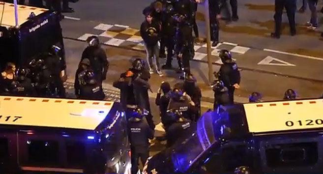 Momento en el que un mosso pone una capucha a un manifestante.