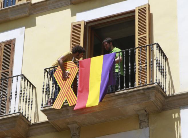 Miembros del grupo municipal de Més cuelgan en su balcón la bandera...