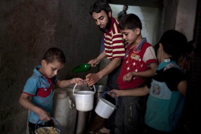 Varios niños recogen la comida dada por una organización benéfica...