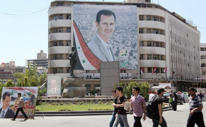Cartel de Bashar Assad en la fachada de un bloque de viviendas en...
