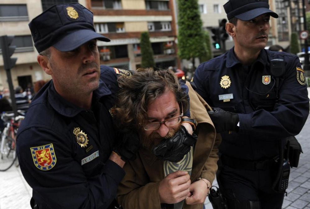 Dos policías sujetan a uno de los manifestantes.