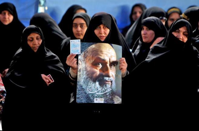 Una mujer iraní sujeta un cartel con la imagen de Jomeini,  en la...