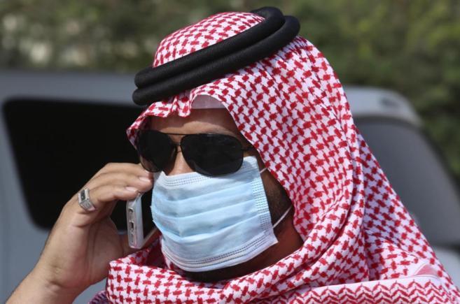 Un hombre con mascarilla habla por el móvil en la ciudad de Jeddah.