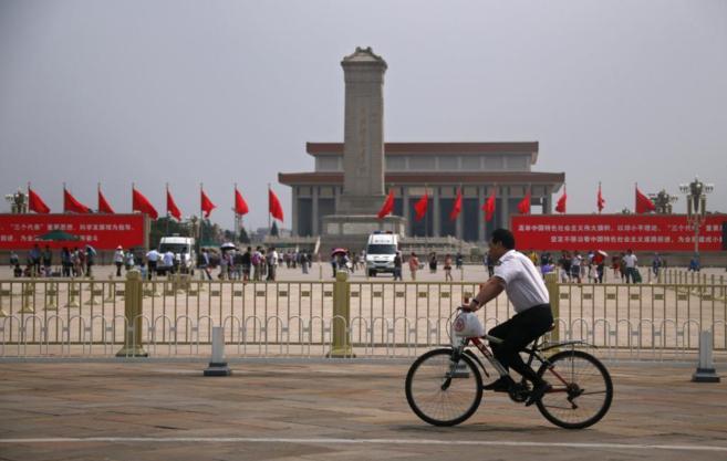 Un hombre circula en bicicleta por la plaza de Tiananmen en la...