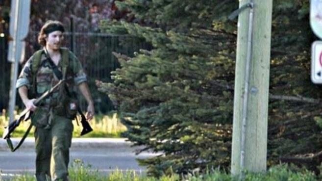 Justin Bourque camina por la calle vestido de militar y con varios...