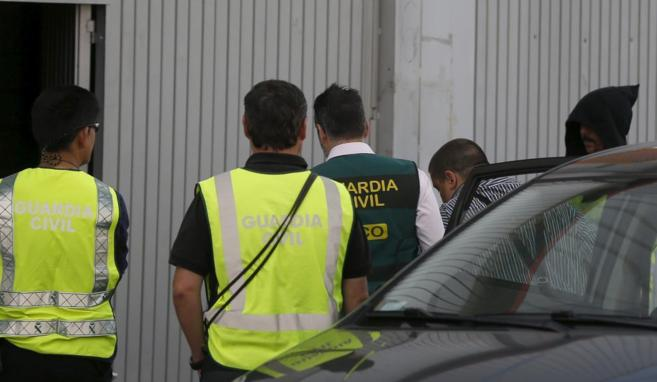 Uno de los detenidos muestra la entrada de su empresa a los agentes,...