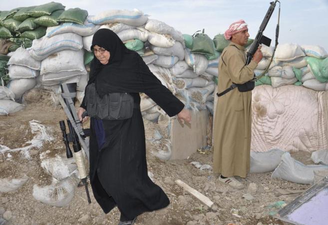 Umm Muayad camina con su rifle durante los choques con Al Qaeda y...