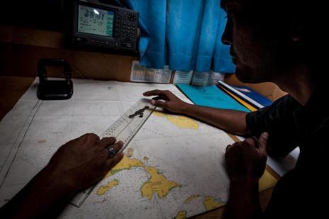 Oficiales indonesios estudian un mapa durante la búsqueda del avión.