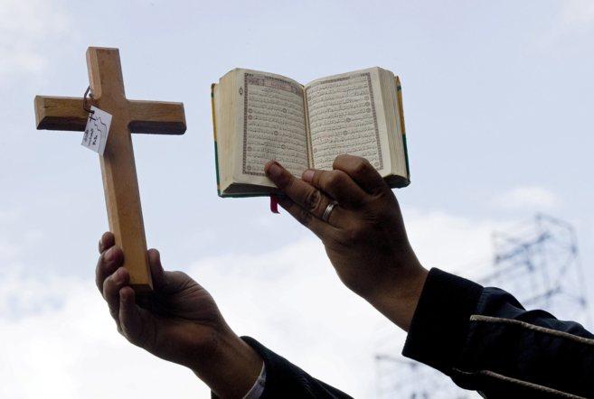 Un manifestante antigubernamental sostiene una cruz y un Corán en la...