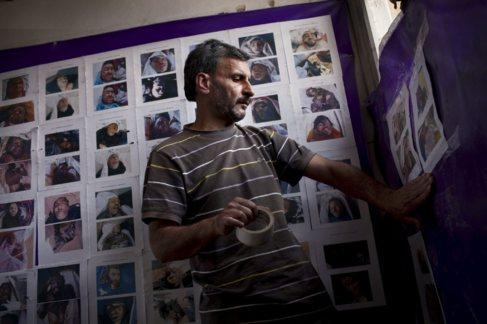 Un miembro del equipo coloca en el muro fotos de cadáveres sin...